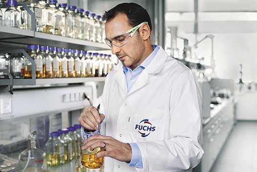 Frank Thomas, Head of Development of FUCHS, standing in the laboratory of FUCHS and holding a container filled with high-grade cutting fluid, a product of FUCHS .